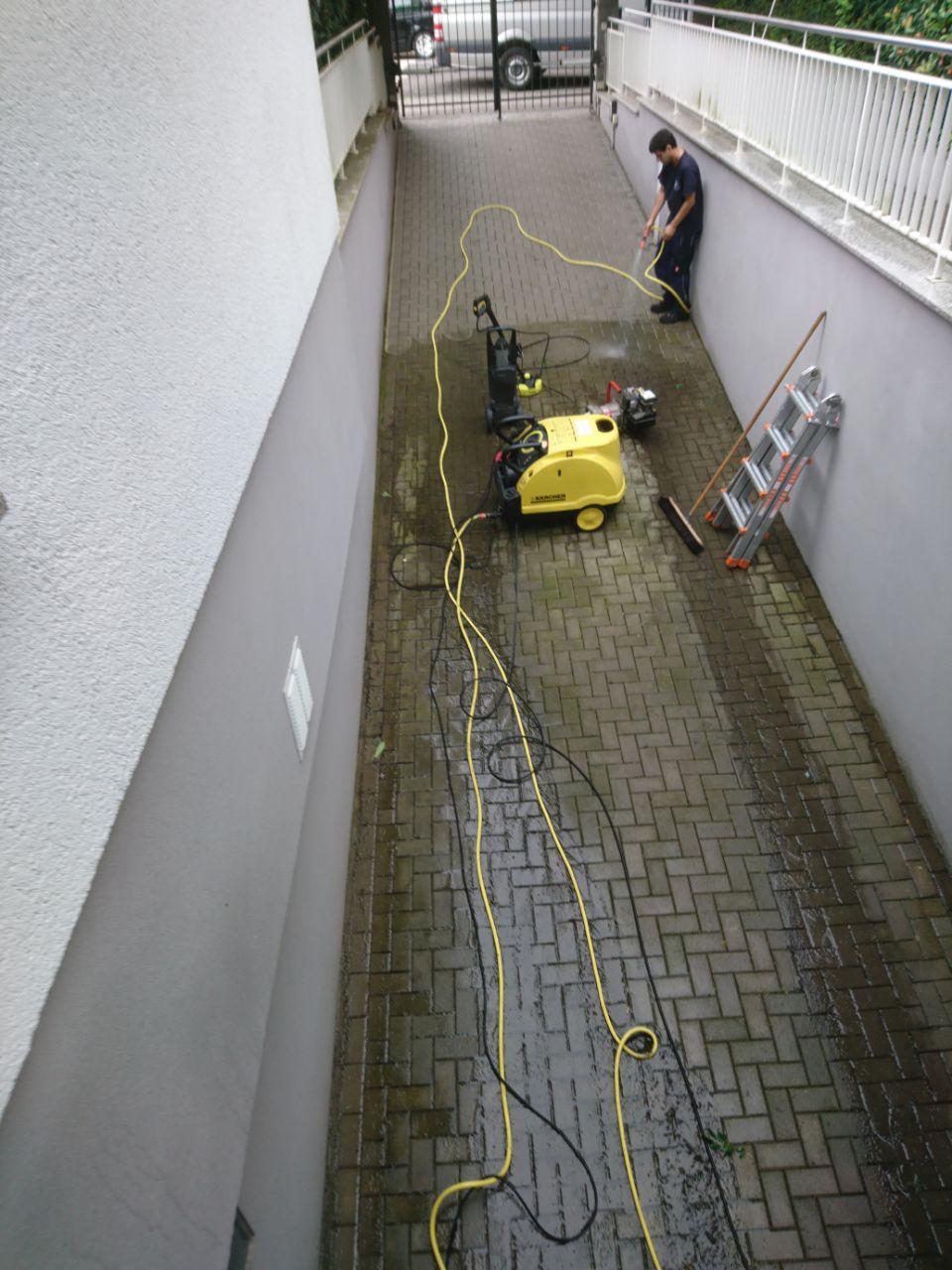 Ein Arbeiter reinigt mit einem Hochdruckreiniger eine Tiefgarageneinfahrt.