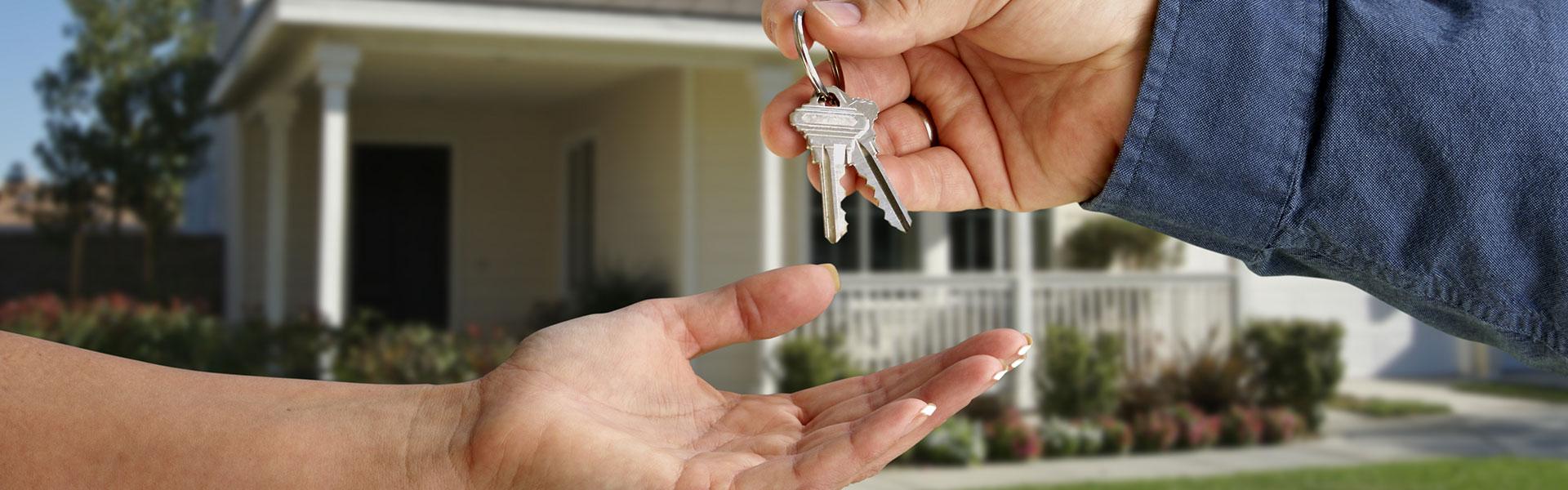Vor einem Haus wird ein Schlüssel von einer in die andere Hand übergeben.